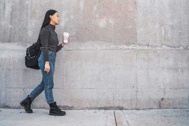 Mujer asiática caminando y sosteniendo una taza de café.