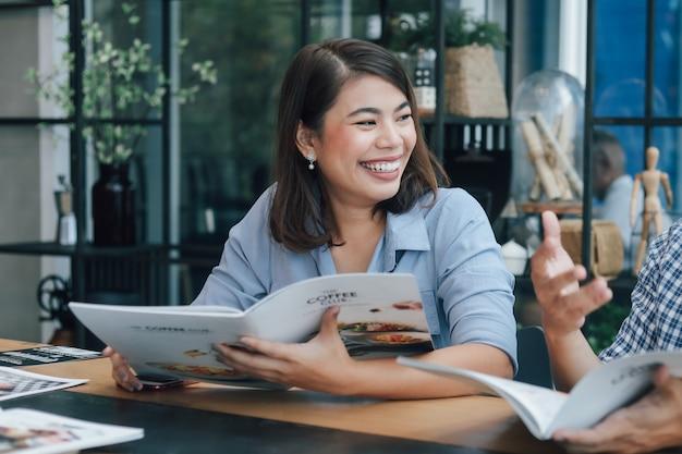 Mujer asiática en camisa azul en la cafetería tomando café y hablando con una sonrisa de novio y cara feliz