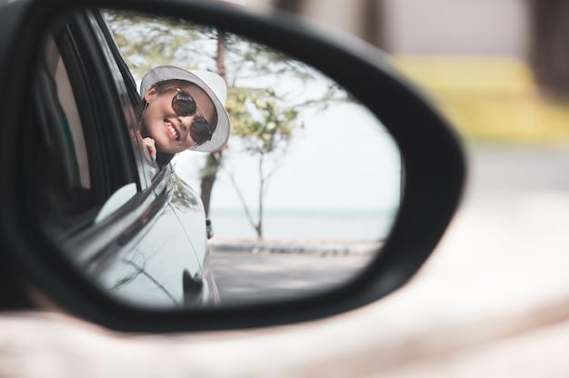 La mujer asiática en la camisa blanca está mirando en el espejo de la vista lateral y está sonriendo mientras que se sienta en su coche, concepto del viaje.