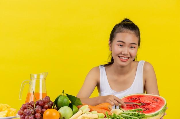 Una mujer asiática con una camiseta blanca está comiendo sandía y la mesa está llena de varias frutas.