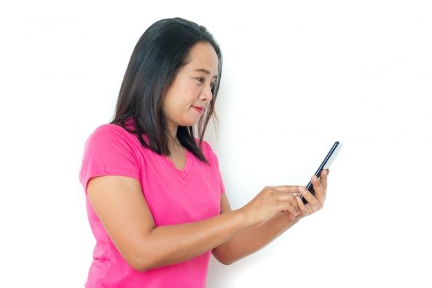 Mujer asiática en camiseta con smartphone sobre el fondo blanco.