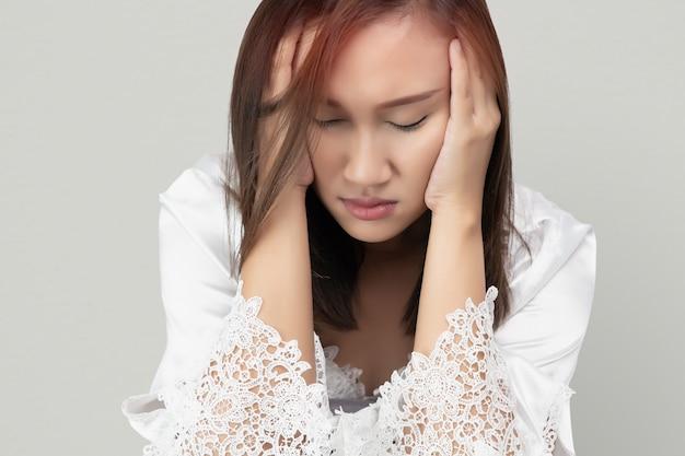 Mujer asiática en camisón de encaje y túnicas de satén blanco tiene dolor de cabeza