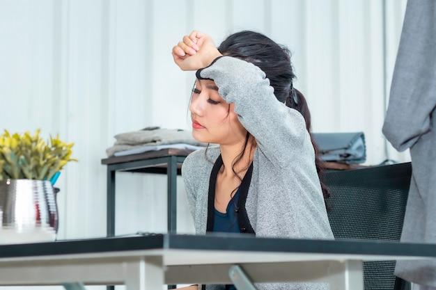 Mujer asiática cansada durante el inicio de trabajo empresario de pequeñas empresas pyme en la tienda de ropa