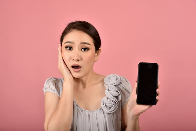 Mujer asiática con cara de expresión dudosa y cuestionadora con teléfono inteligente, noticias falsas y desinformación falsa que se propaga a través de las redes sociales de internet.