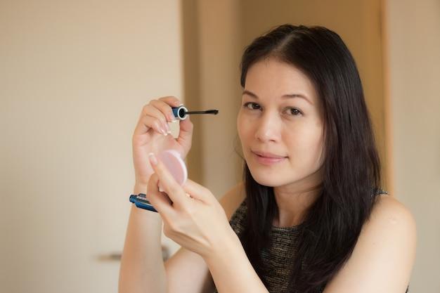 Mujer asiática con el cepillo del maquillaje.