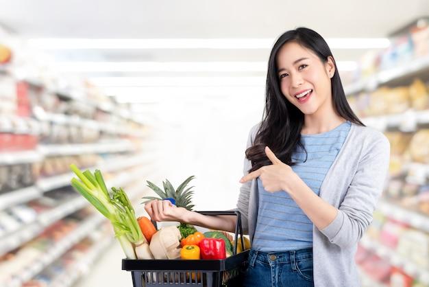 Mujer asiática con la cesta de compras llena de comestibles en supermercado