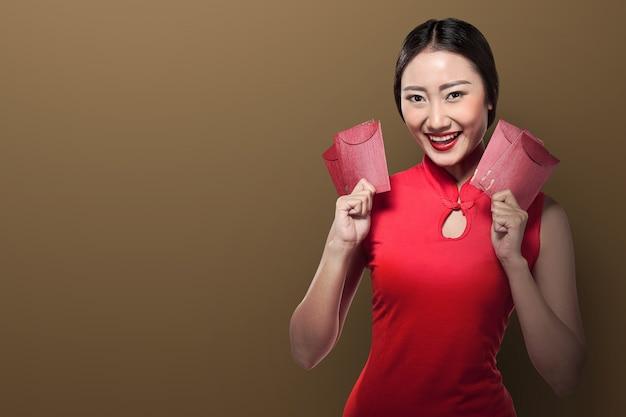 Mujer asiática en cheongsam vestido sosteniendo angpao