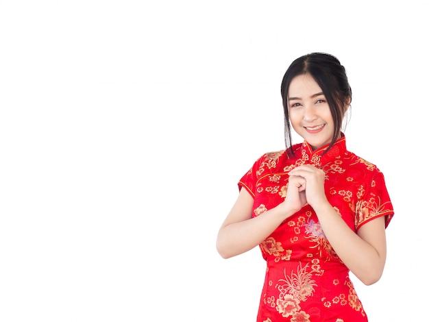 La mujer asiática en chino viste el aislante tradicional del cheongsam en el fondo blanco. año nuevo chino concepto.