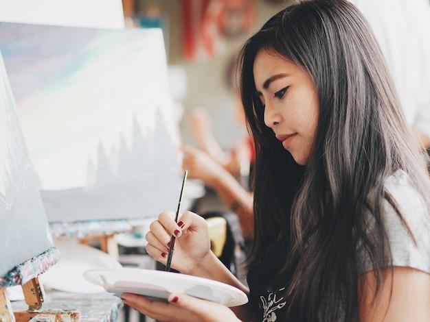 Mujer asiática en clase de pintura