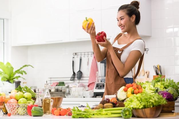 Mujer asiática en una cocina preparando frutas y verduras para una comida saludable y ensalada