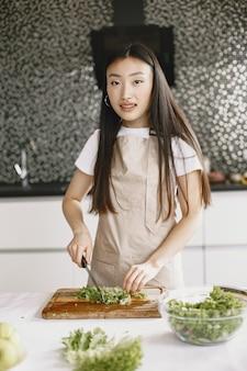 Mujer asiática cocinando en casa.