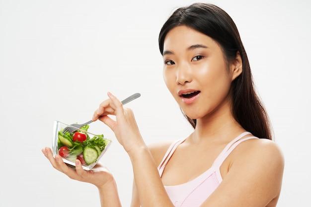 Mujer asiática comiendo ensalada