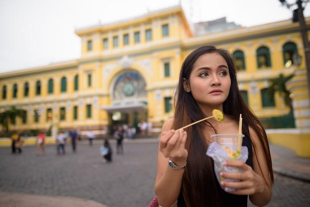 Mujer asiática comiendo frente a la oficina central de correos de saigón
