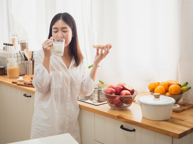 Mujer asiática comiendo pan y beber leche en la cocina