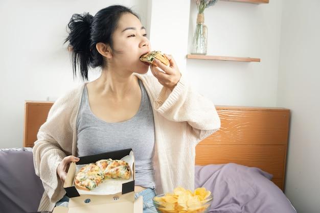 Mujer asiática comiendo pizza y papas fritas sentado en la cama