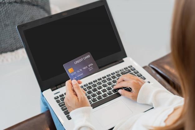Mujer asiática compras en línea con tarjeta de crédito y tableta sentado en el sofá en casa, estilo de vida digital con tecnología, concepto de comercio electrónico