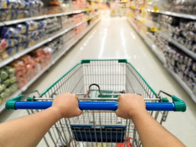 Mujer asiática de compras en la tienda de supermercado con empujar el carrito de compras