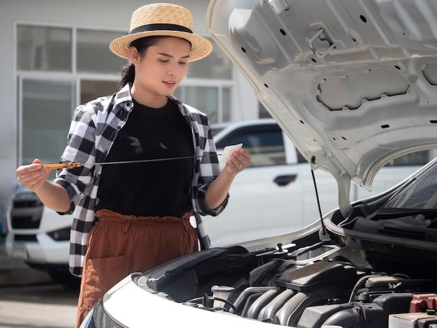 La mujer asiática está comprobando el nivel de aceite en el motor de coche.