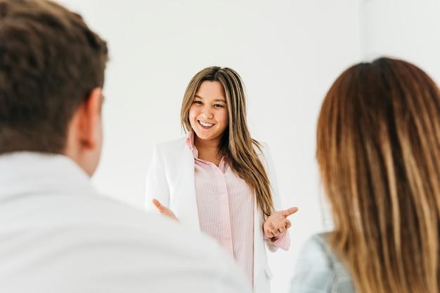 Mujer asiática confiada que hace la presentación para los compañeros de trabajo