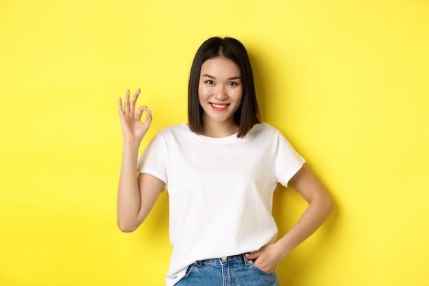 Mujer asiática confiada que sonríe y que muestra el signo ok, aprueba y alaba la buena oferta, de pie en camiseta blanca sobre fondo amarillo.