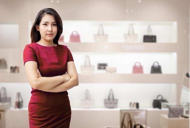 Mujer asiática confiada en tienda del bolso de la moda