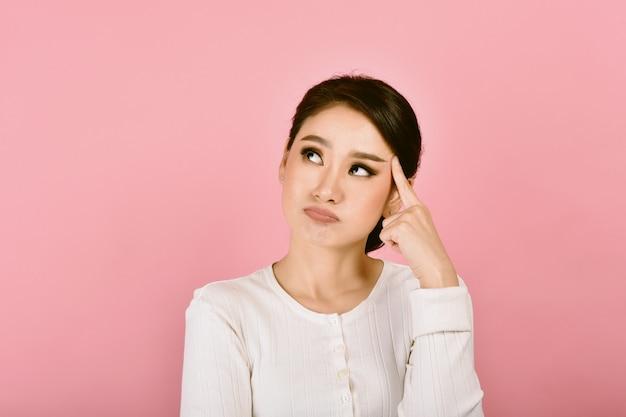 Mujer asiática confundida y mareada pensativa, expresión de la cara sensación de preocupación problemas desordenados