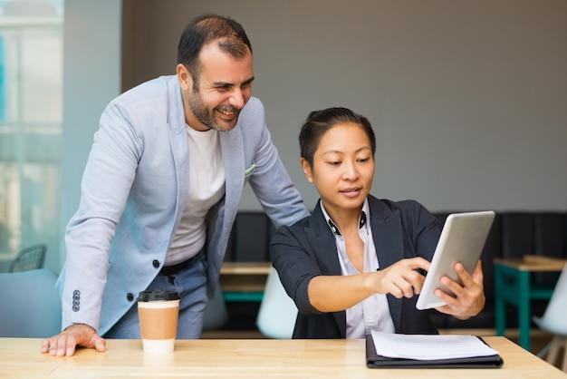 Mujer asiática contenta que muestra la presentación en línea en la tableta
