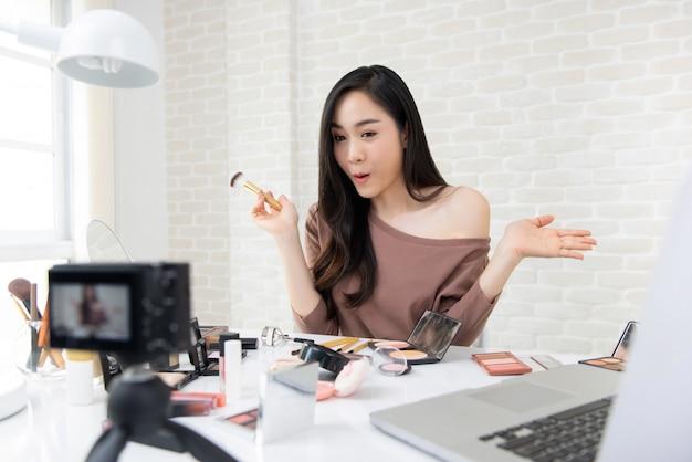 Mujer asiática cosmética y belleza blogger grabación maquillaje revisión video