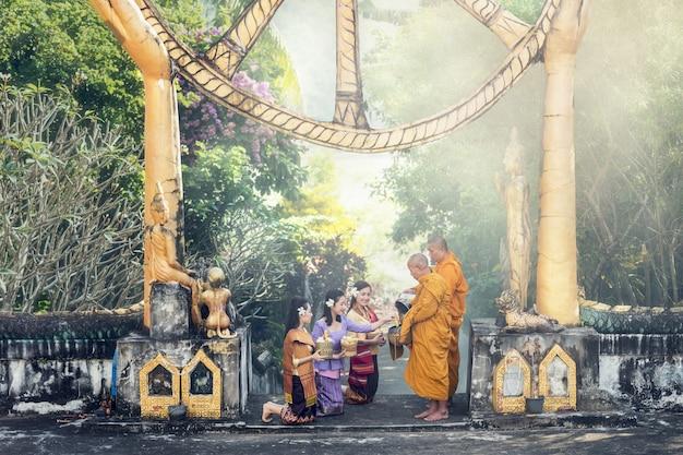 Mujer asiática da ofrendas de comida a monjes budistas