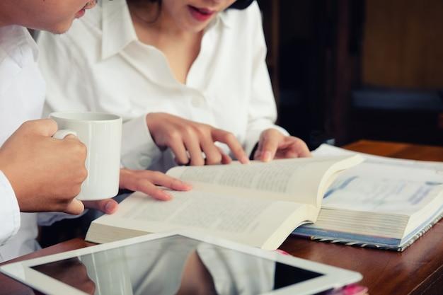 Mujer asiática del primer que lee el libro de texto y la tableta en biblioteca.