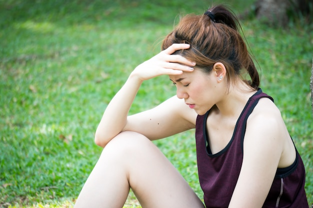 La mujer asiática del deporte tiene dolor de cabeza después de correr en el parque al aire libre