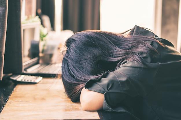Mujer asiática deprimida sentada sola en la habitación
