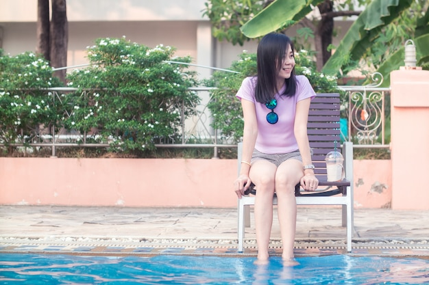 Mujer asiática descansando en la piscina con ambos pies en el agua