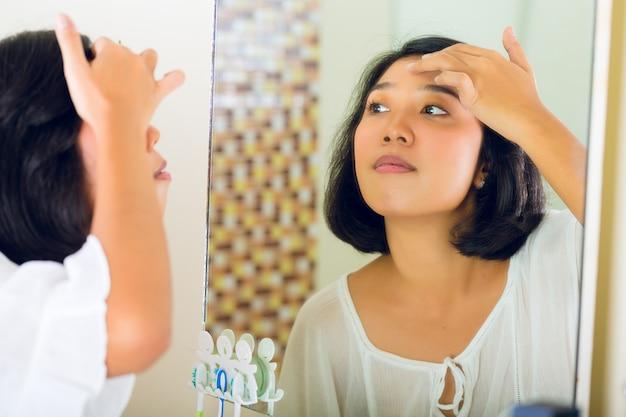 Mujer asiática descubriendo un grano en la cara