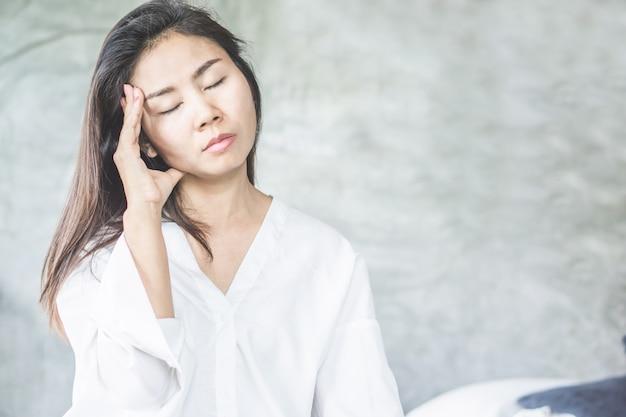 Mujer asiática despierta con dolor de cabeza de migraña