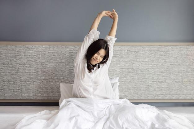 Mujer asiática se despierta y estira el brazo en su cama por la mañana