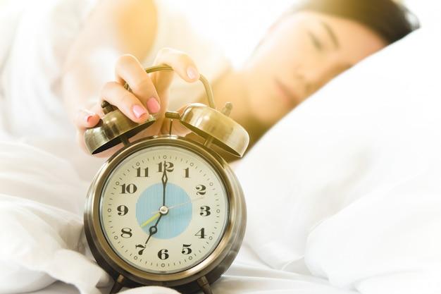 Mujer asiática despierta en la mañana por el reloj de alarma