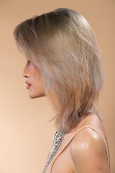 Mujer asiática después de aplicar maquillaje estilo de pelo gris plateado. sin retoques, rostro fresco con acné, labios, ojos. iluminación de estudio de fondo amarillo beige, para tratamiento de terapia estética, vista trasera