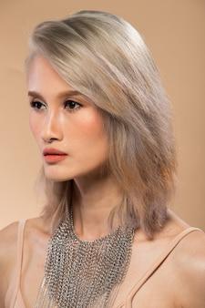 Mujer asiática después de aplicar maquillaje estilo de pelo gris plateado. sin retoques, rostro fresco con labios, ojos, mejillas, piel suave y agradable. estudio de iluminación de fondo amarillo beige, para tratamiento de terapia estética