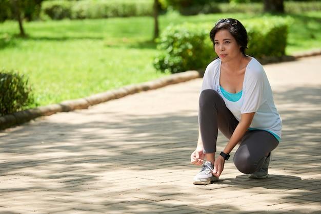 Mujer asiática deteniéndose mientras trota