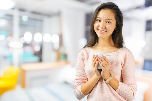 Mujer asiática disfruta con una taza de café