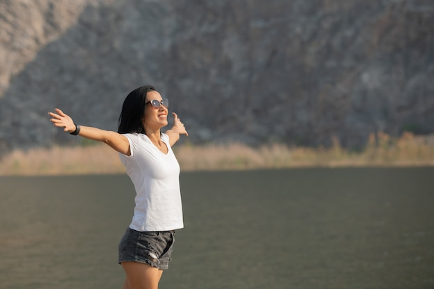 Mujer asiática disfrutando de la belleza de la naturaleza mirando el lago de la montaña