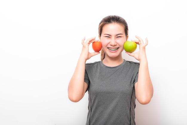 Mujer asiática divirtiéndose con manzana verde y tomate