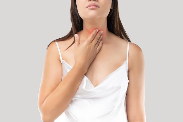 Mujer asiática con dolor de garganta o glándula tiroides contra el gris.