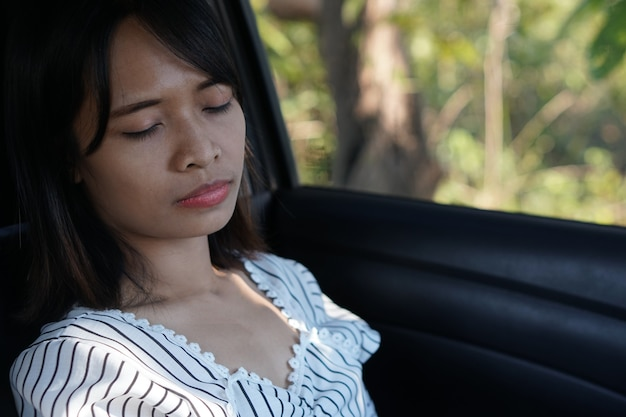 Mujer asiática durmiendo en un auto