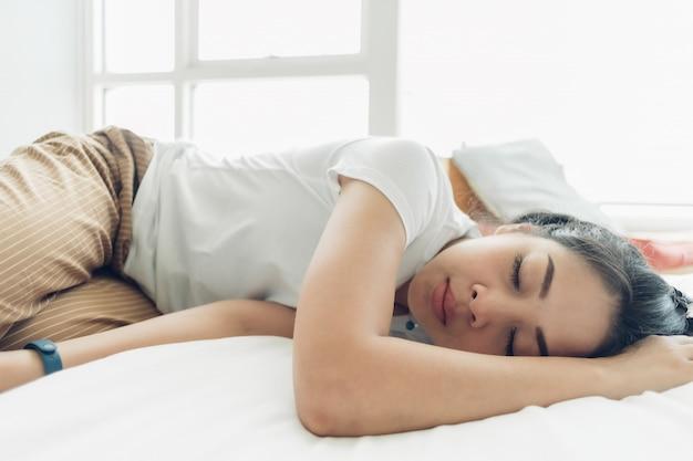 La mujer asiática está durmiendo en su cama blanca y acogedora.