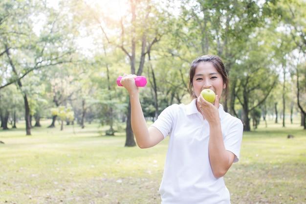 Mujer asiática ejercicio y entrenamiento levantando peso o pesa rosa en el parque