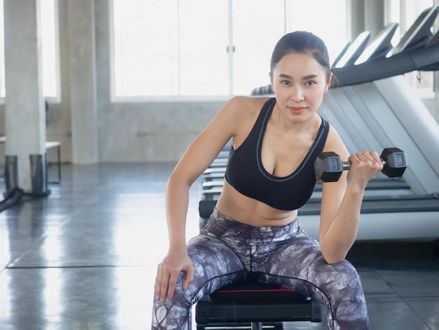 La mujer asiática está ejercitando con una pesa de gimnasia en gimnasio