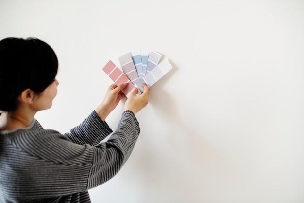 Mujer asiática eligiendo el color de la pared