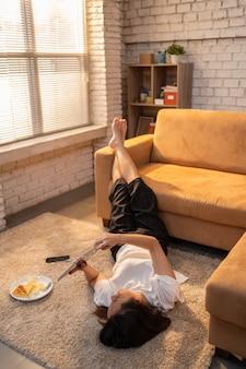 Mujer asiática ella trabaja desde casa, se relaja, usa las redes sociales. siga las noticias y relájese.